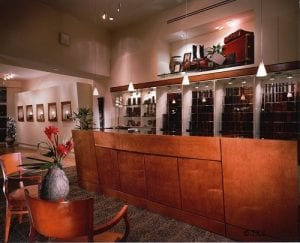 "Custom Belt and ""Buckle Bar"" where customers can select the leather that is hanging on the back wall and their silver or gold buckle that is displayed inside the bar cabinet under glass. This design feature was essential so that customers could not handle the expensive leather and damage it with hand oil or dirt."